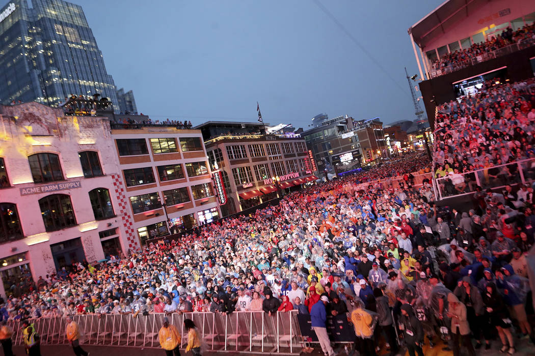 Fans line up Broadway in the rain to watch the first round of the NFL football draft, in Nashvi ...