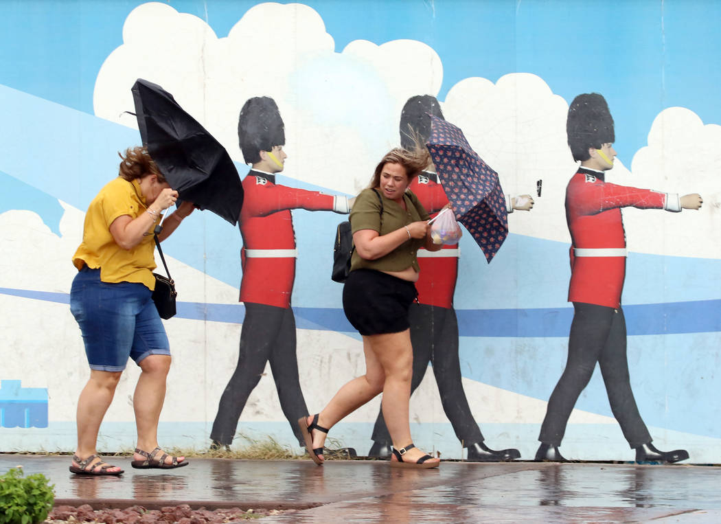 Pedestrians hold umbrellas to protect themselves from heavy winds and rain as they walk along L ...
