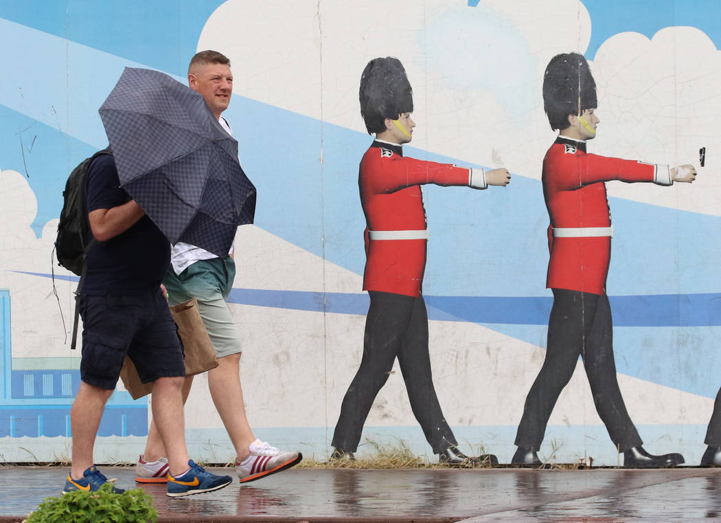 A pedestrian holds an umbrella to protect himself from heavy winds and rain as he walks along L ...