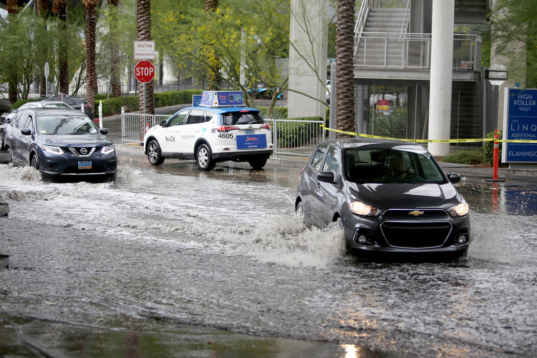 Cars drive through the flooding at The Linq Hotel and casino parking garage in Las Vegas, Monda ...
