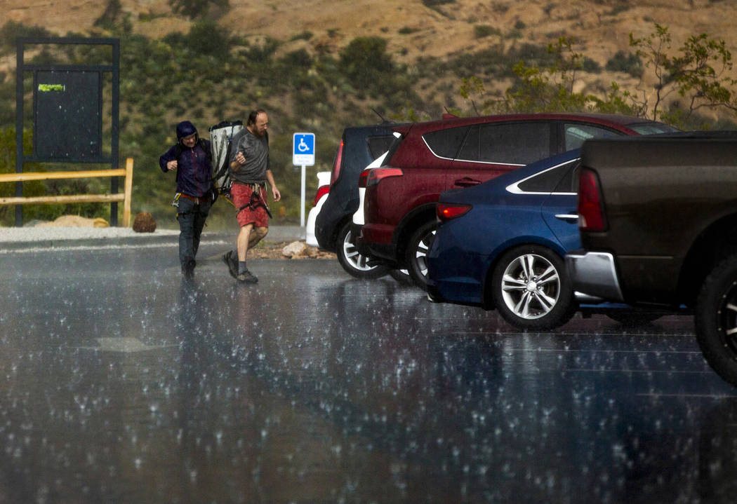 Hikers run for their vehicle as a fast-moving storm makes its way through the Red Rock Canyon N ...