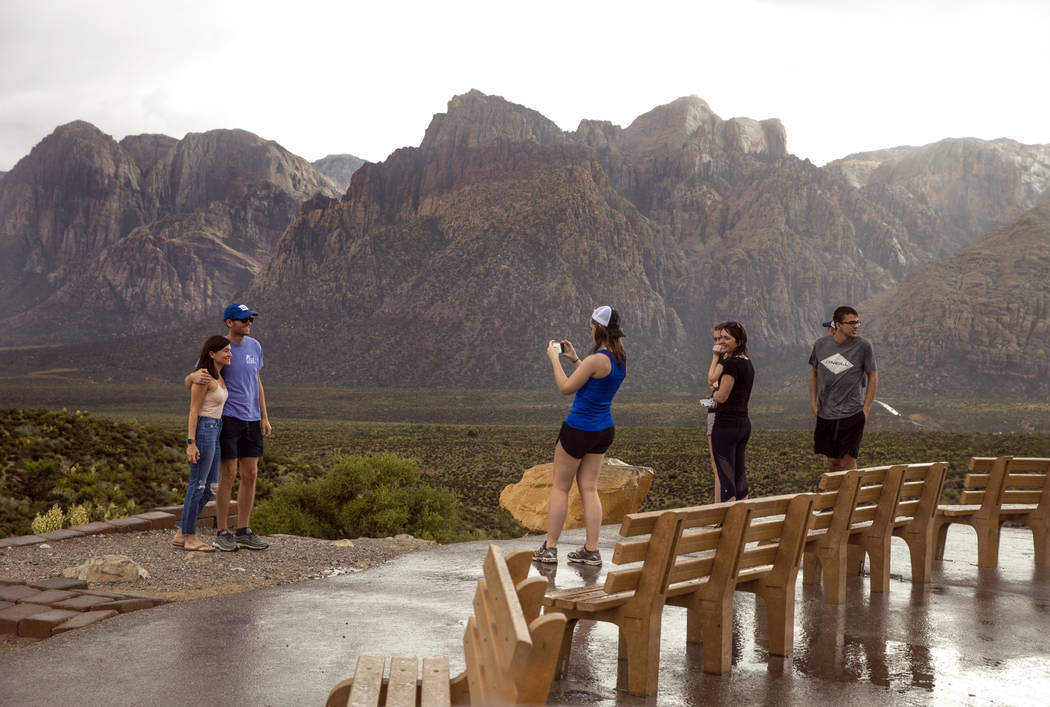 Visitors brave the rain for some photos as a fast-moving storm makes its way through the Red Ro ...