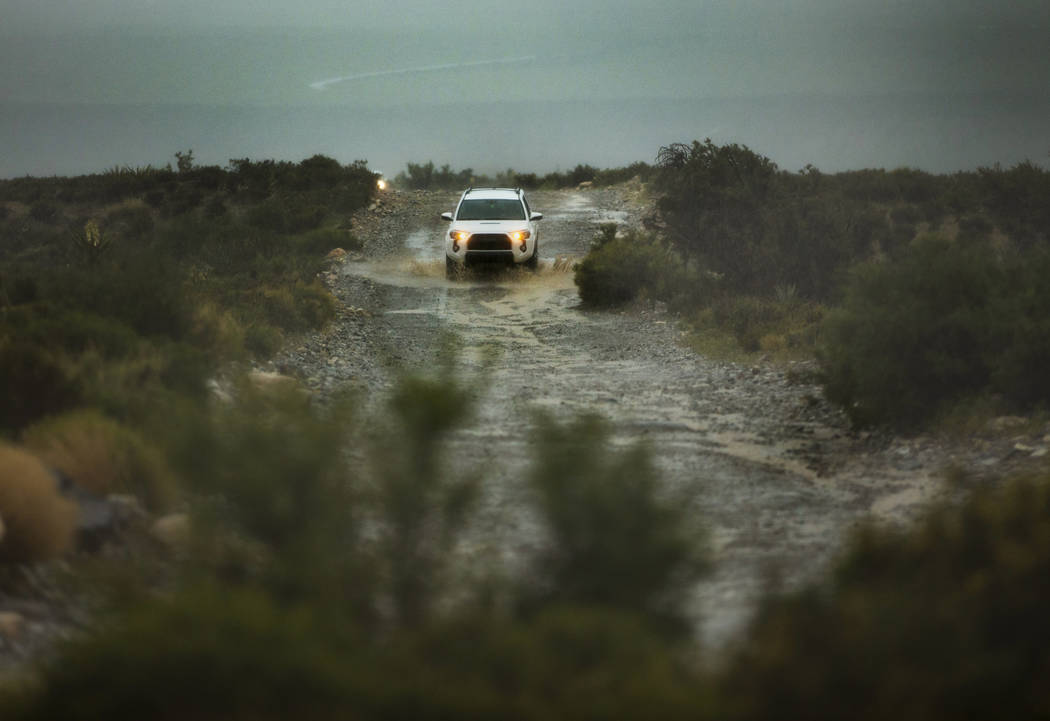 Visitors brave a rain-soaked gravel road as a fast-moving storm makes its way through the Red R ...