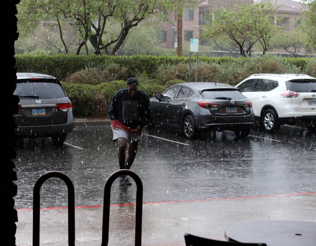 Khirie Williams of Las Vegas runs through a downpour at Summerlin Center Pointe Plaza in Las Ve ...