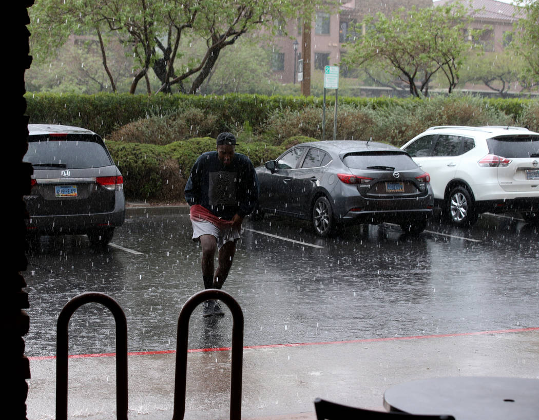 Khirie Williams of Las Vegas runs through a downpour at Summerlin Center Pointe Plaza in Las Ve ...