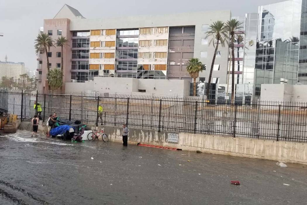 People try to get out of the rain in a wash near the Hard Rock Hotel in Las Vegas, Monday, Apri ...