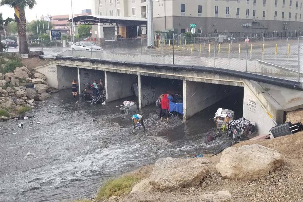 People try to get out of the rain in a wash near Flamingo Road and Palos Verdes Street in Las V ...