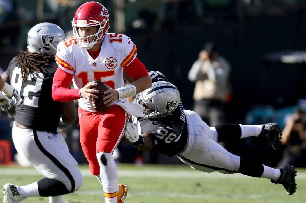 Kansas City Chiefs quarterback Patrick Mahomes (15) sheds tackle by Oakland Raiders defensive e ...