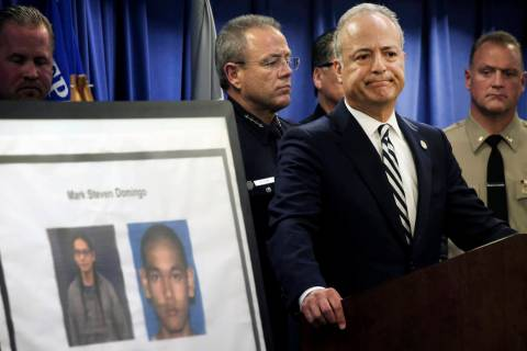 United States Attorney Nick Hanna stands next to photos of Mark Steven Domingo, during a news c ...