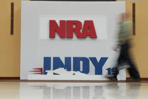 A visitor to the at the National Rifle Association Annual Meeting walks past signage for the ev ...