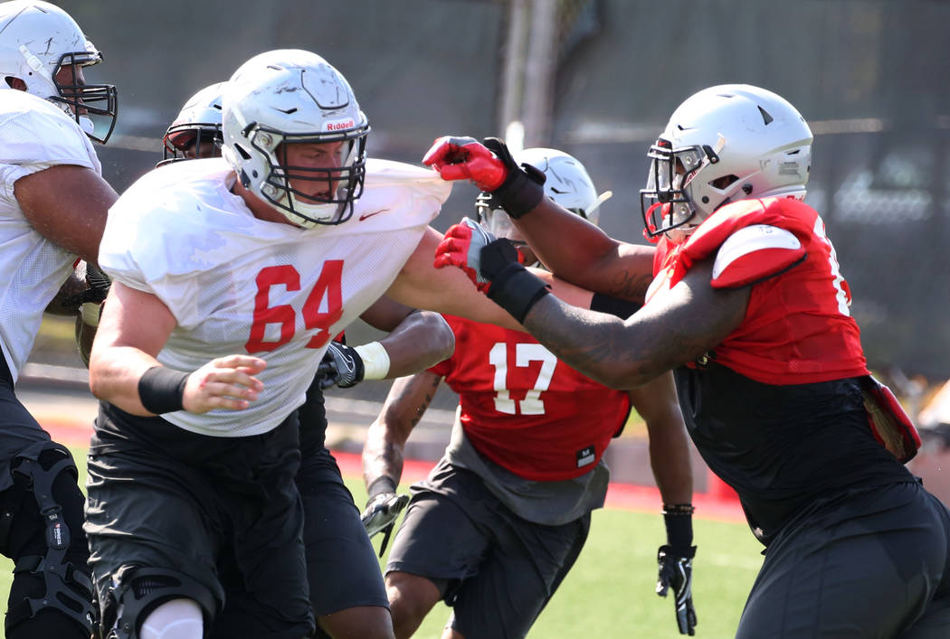 UNLV's defensive end Jameer Outsey, right, defends offensive lineman Nathan Jacobson (64) durin ...