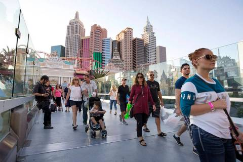 People walk over a pedestrian bridge linking New York-New York and MGM Grand near the intersect ...