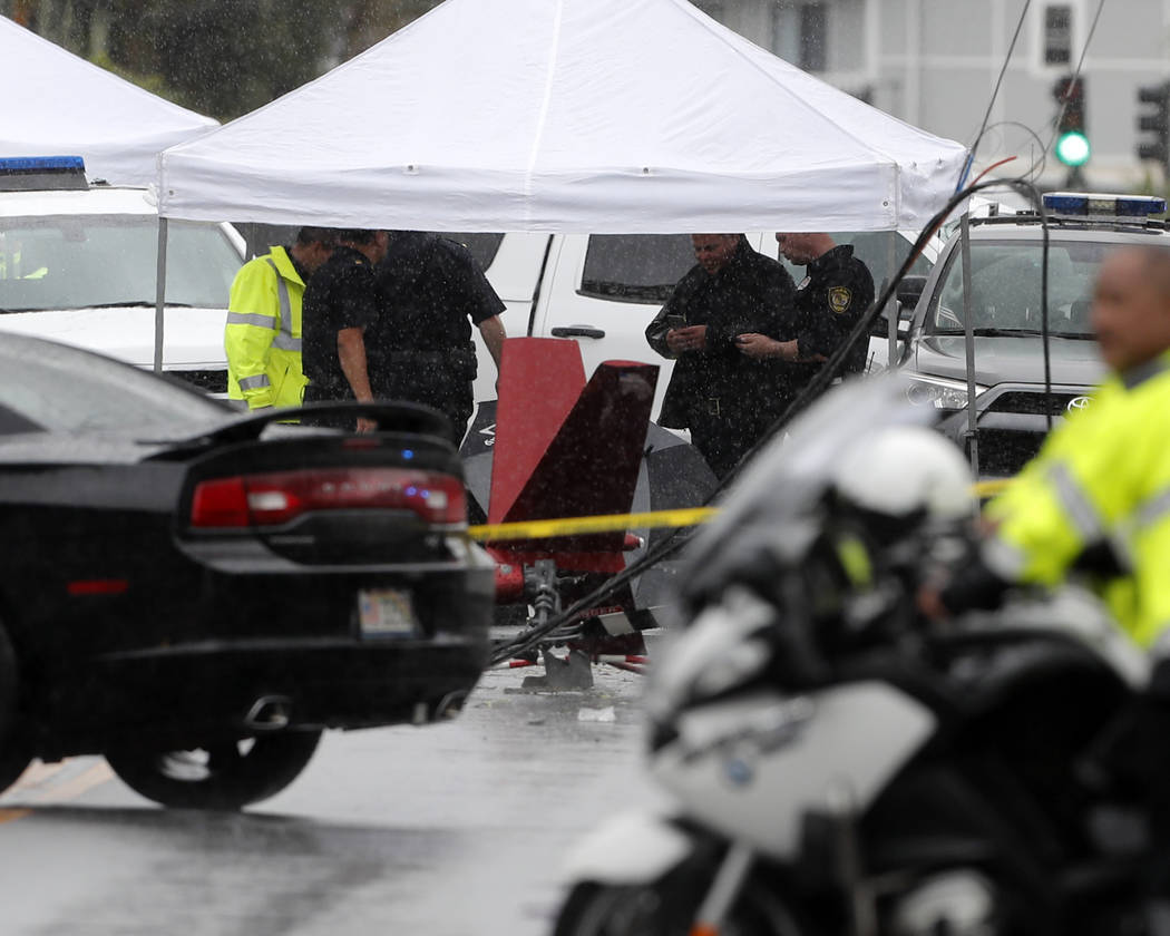 Investigators stand around the wreckage of a helicopter, Monday, April 29, 2019, in Kailua, Haw ...
