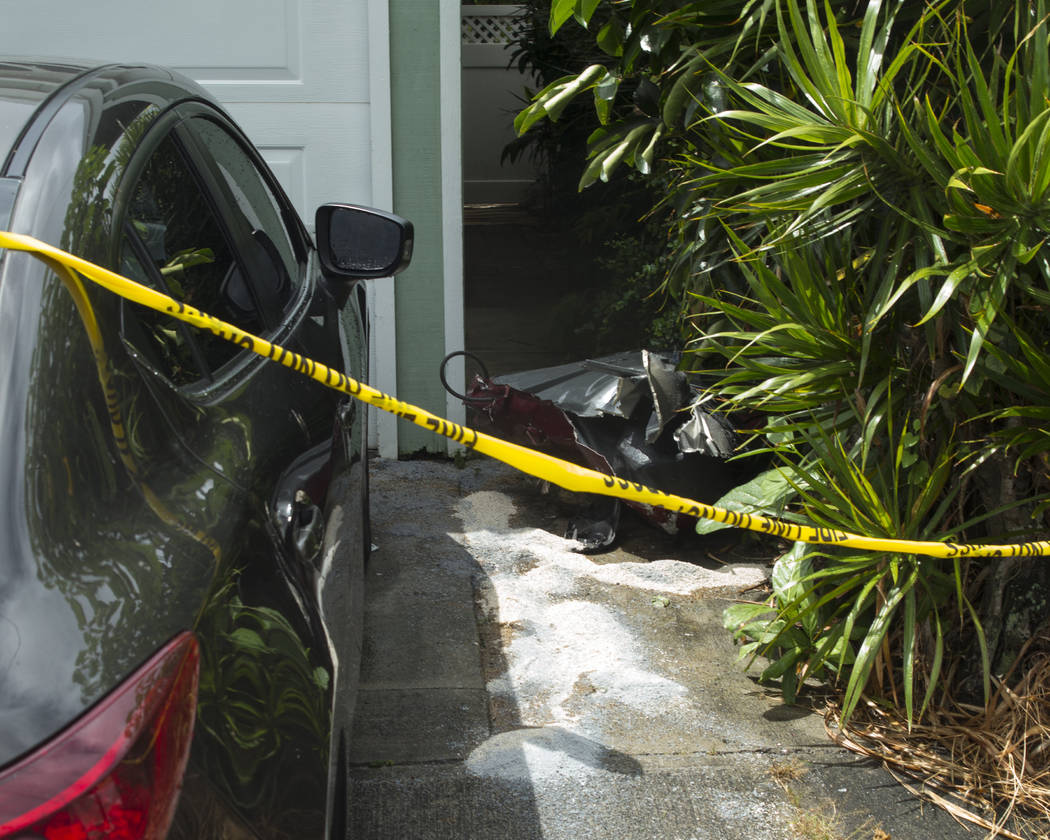 Debris lays on the ground where parts of a helicopter hit a parked car, Monday, April 29, 2019, ...