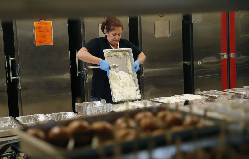In this March 25, 2019, photo, Lisa Garcia packs up uneaten food from the convention area at th ...