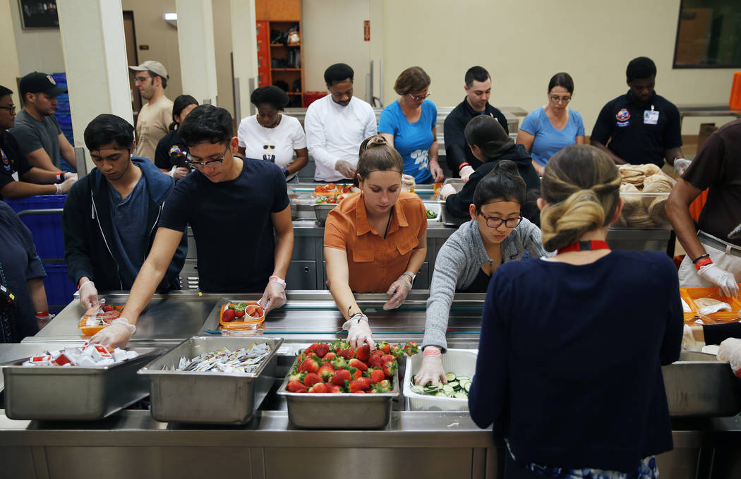 In this March 26, 2019, photo, volunteers put together food trays at Three Square, a food bank ...
