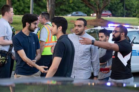 People gather across from the campus of University of North Carolina at Charlotte after a shoot ...