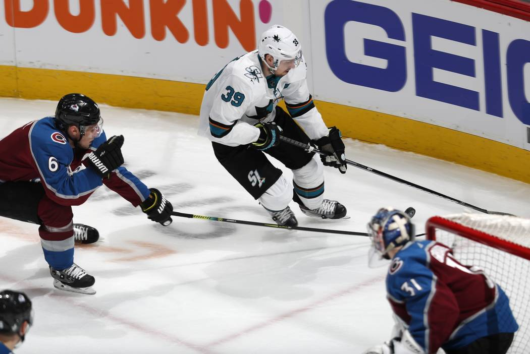 San Jose Sharks center Logan Couture, back right, drives to the net with the puck as Colorado A ...