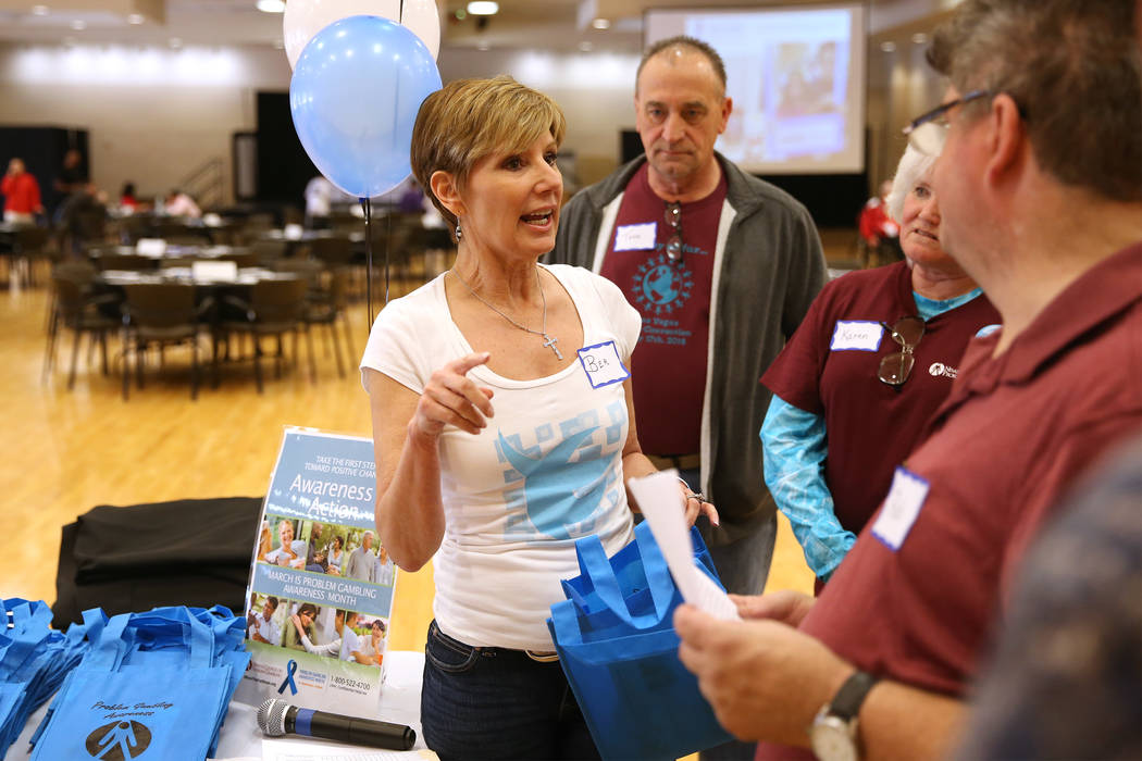 Bea Aikens, center, gives directions during a National Problem Gambling Awareness Month event a ...