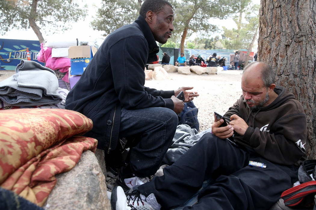 Hachet, right, works on a phone belonging to Michael Fletcher at the City of Las Vegas Courtyar ...