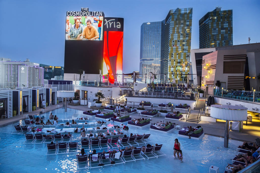 Pool goers enjoy a showing of Happy Gilmore during Dive in Movies at Boulevard Pool on Monday, ...