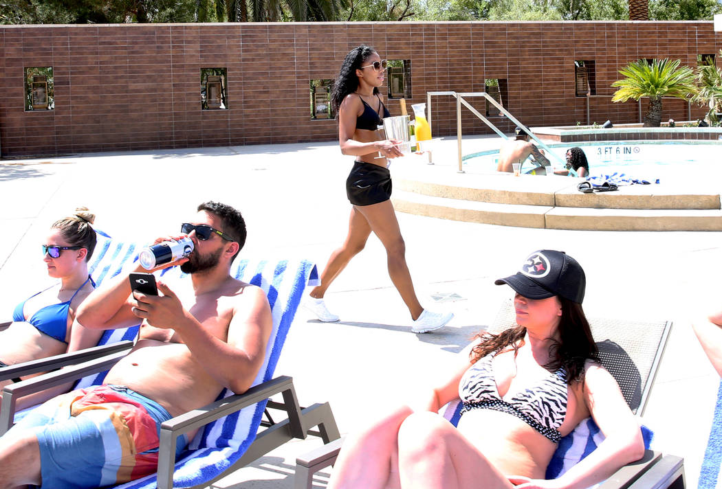 Ocie Hood, model cocktail server, delivers drinks to hotel guests at M Resort Spa Casino pool a ...