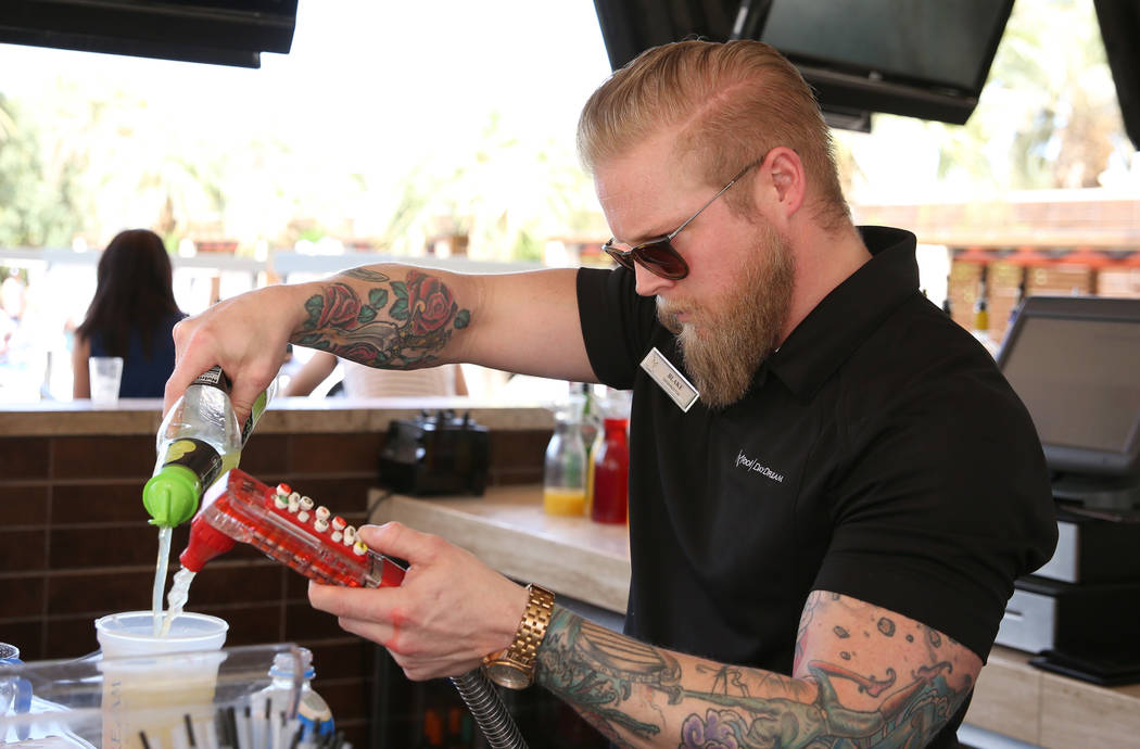 Blake Brown, a bartender, mixes drinks at M Resort Spa Casino pool area on Saturday, April 27, ...