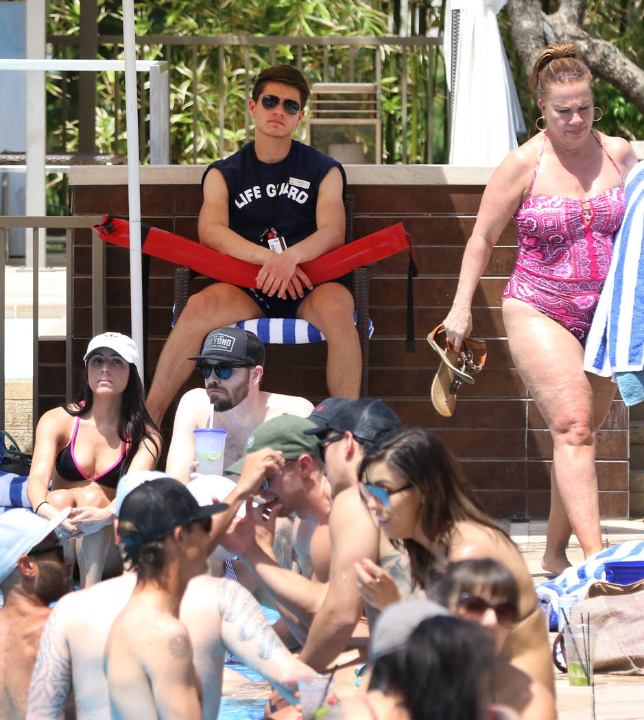 Life guard Thomas Flannery watches as hotel guests relax at M Resort Spa Casino pool on Saturda ...