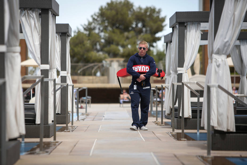 Lifeguard Vance Ferron walks out by the pool at the M Resort in Henderson, Thursday, April 4, 2 ...