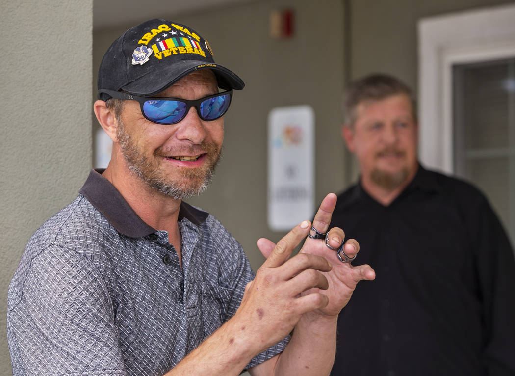 Friends Christian Bridges and Ron Cochran chat outside their apartments in Las Vegas on Monday, ...