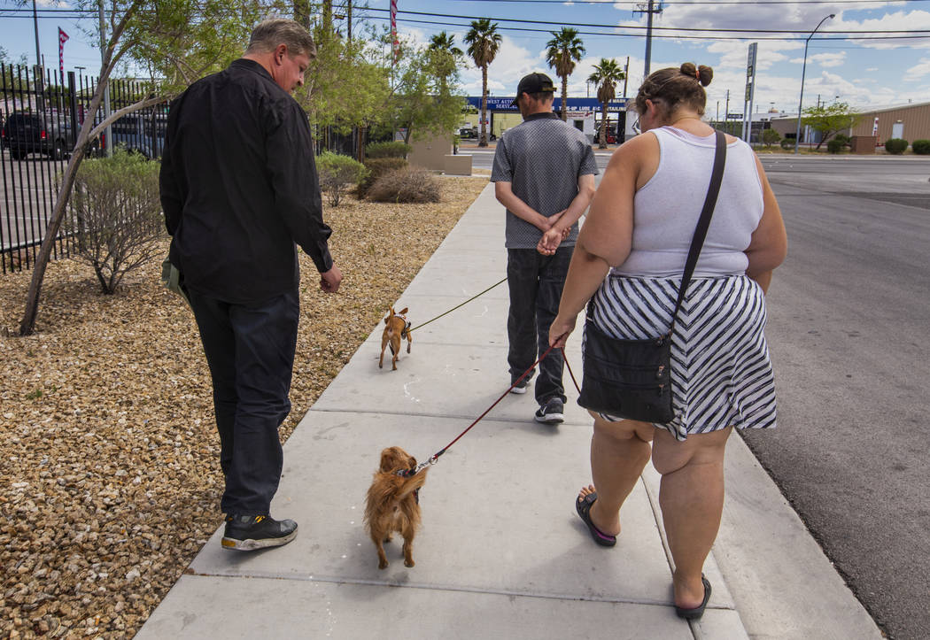 Ron Cochran, with his dog Cookie, visits with friends Christian Bridges and Rebecca Zima-Reinha ...