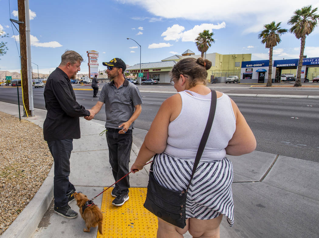 Ron Cochran, with his dog Cookie, says goodbye for the day with friends Christian Bridges and R ...