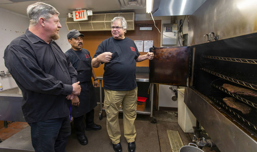 New employee Ron Cochran receives some smoker training from kitchen manager Alvaro Hernandez an ...