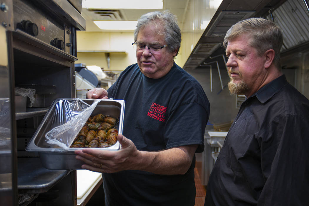 """Owner Paul Reddick shows new employee Ron Cochran what they call """"wolf turds"""" in the kitchen at ..."""