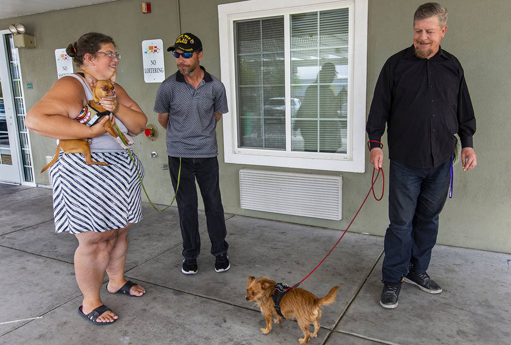 Ron Cochran, from right, with his dog Cookie, visits with friends Christian Bridges and Rebecca ...