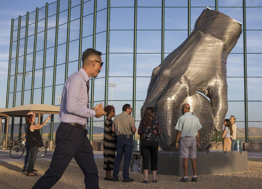 """Artist Luis Varela-Rico, left, passes by his sculpture """"Organic Study No. 2"""" during a ..."""