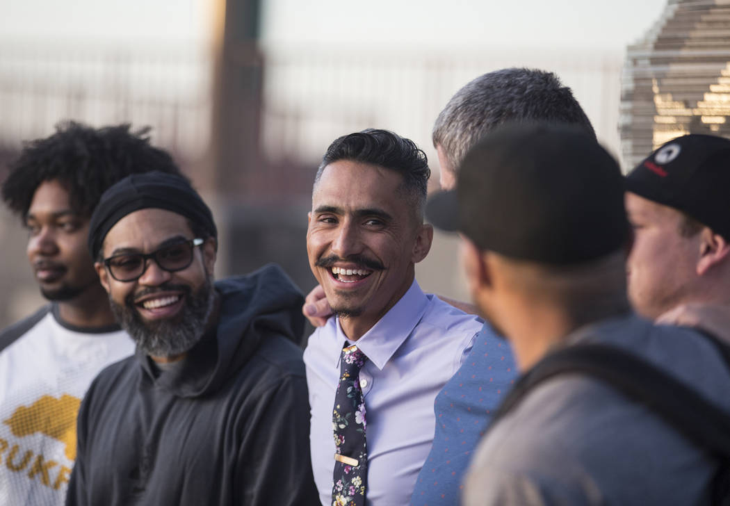 Artist Luis Varela-Rico, middle, jokes around with friends during a dedication ceremony for hi ...