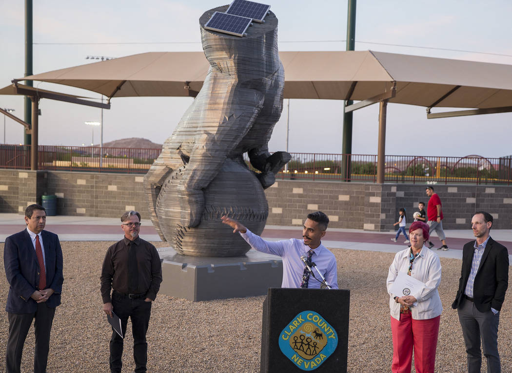 """Artist Luis Varela-Rico, middle, speaks during a dedication ceremony for his sculpture """"Or ..."""