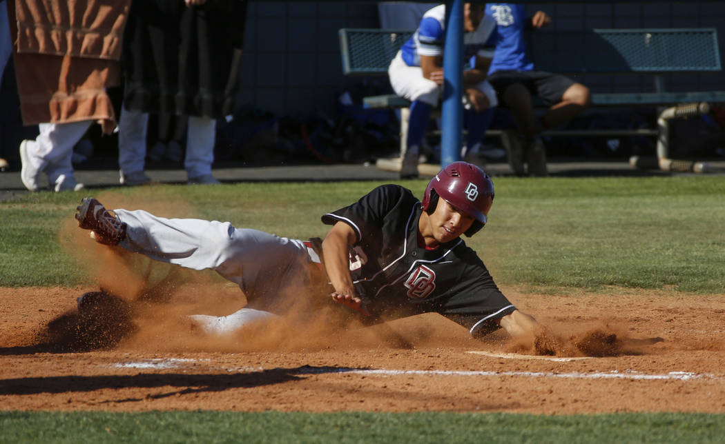 Desert Oasis outfielder Tripp Edens (3) slides into home base in the third inning of a baseball ...