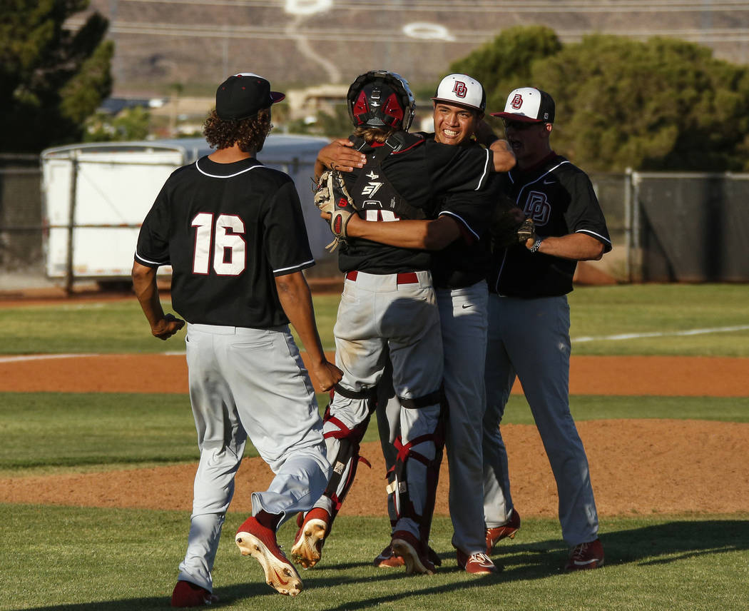Desert Oasis pitcher Aaron Roberts (25) in congratulated by his teammates after beating Basic H ...