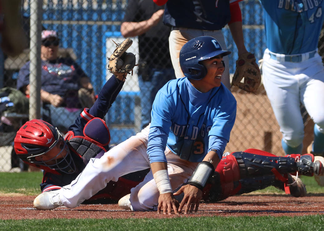 Centennial's Anthony Martinez, left, avoids a tag from Liberty's catcher James Katona as he sco ...
