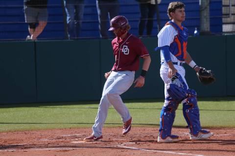 Desert Oasis Parker Schmidt (4) runs home for a run as Bishop Gorman's Gavin Mez (18) looks on ...
