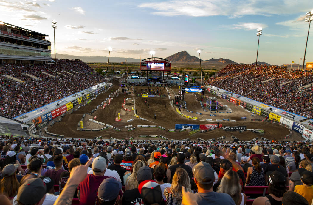 Motorcycles blur by during the featured 450 SX class race at Sam Boyd Stadium on Saturday, May ...