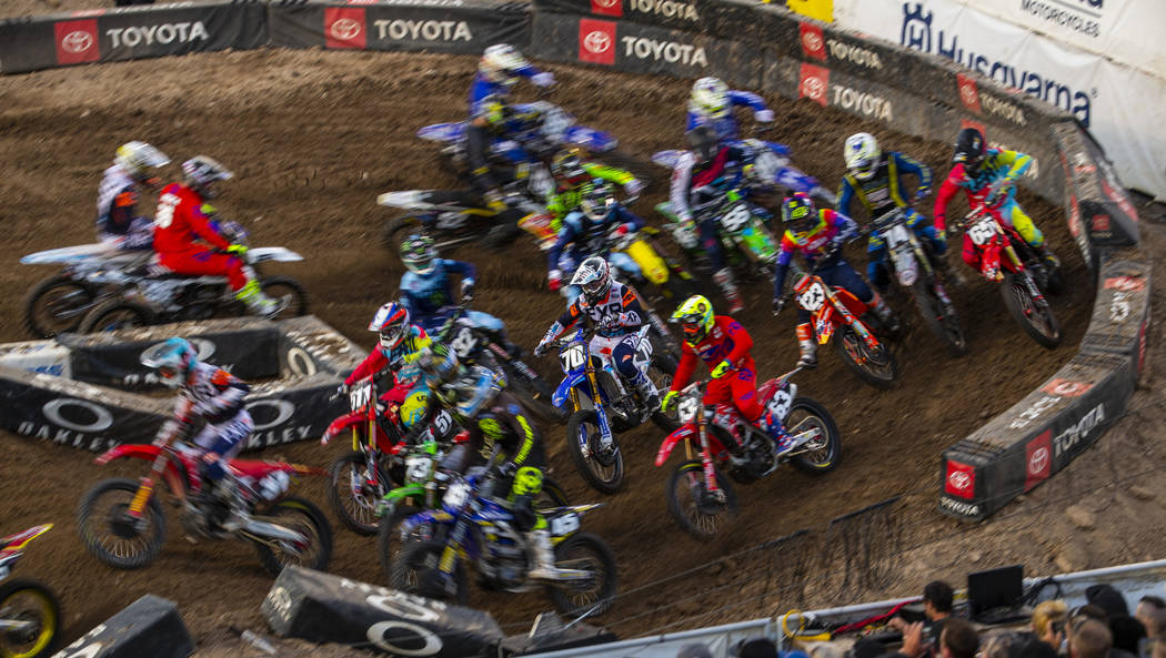 Riders blur through the fist main turn during the featured 250 SX class race at Sam Boyd Stadiu ...