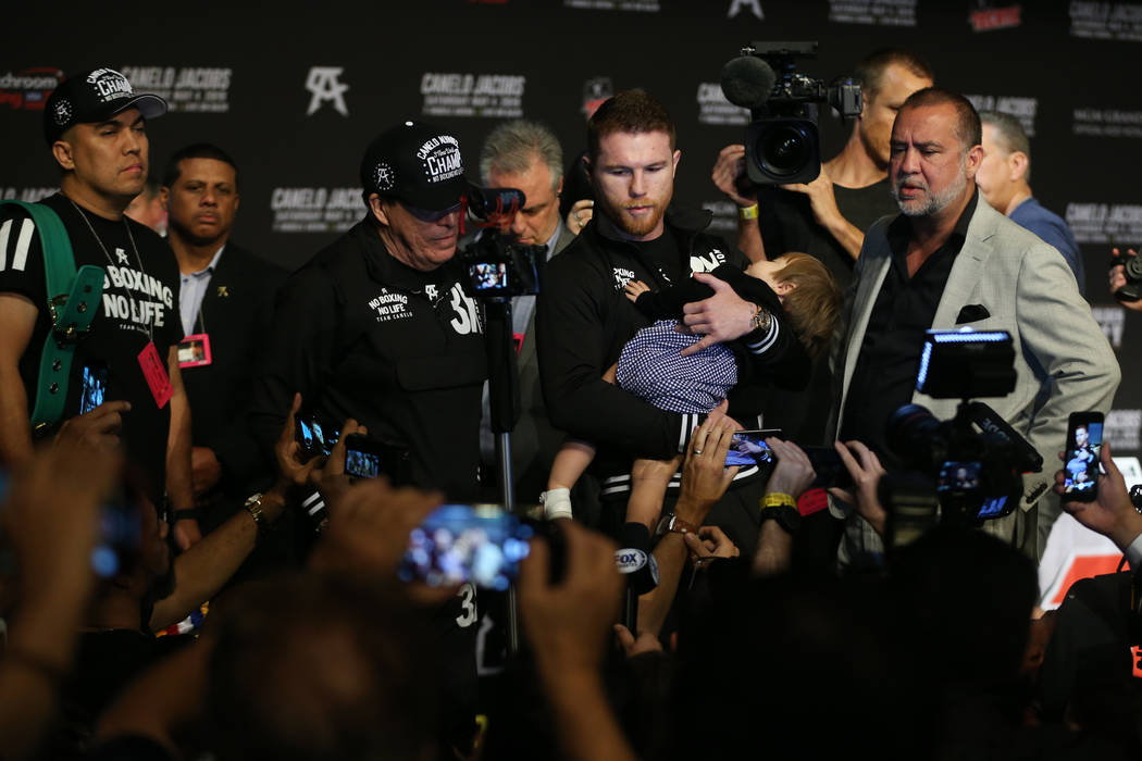 """Saul """"Canelo"""" Alvarez holds his daughter Emily as he speaks to reporters during a pre ..."""