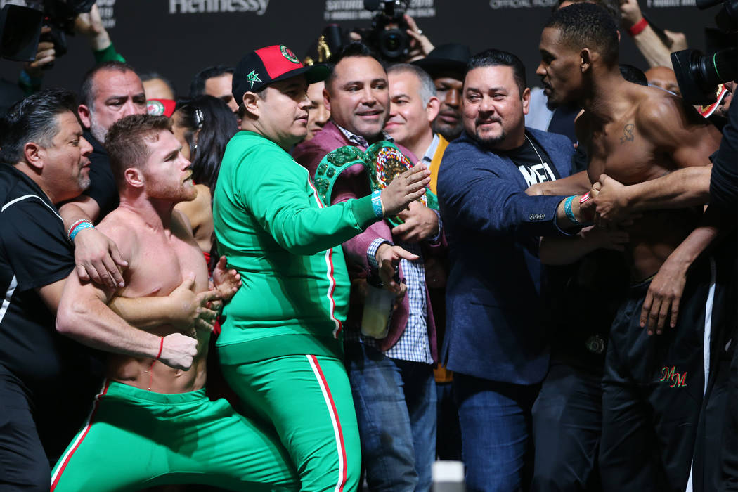 """Saul """"Canelo"""" Alvarez, left, and Daniel Jacobs, get into a scuffle during their weigh ..."""