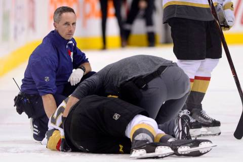 A trainer attends to Vegas Golden Knights center Erik Haula (56), who had taken a hit along the ...