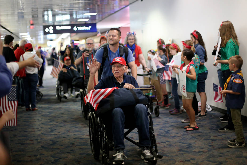 Veteran Dean Whitaker, with guardian Jason Frederico, greets people as they welcome him back fr ...