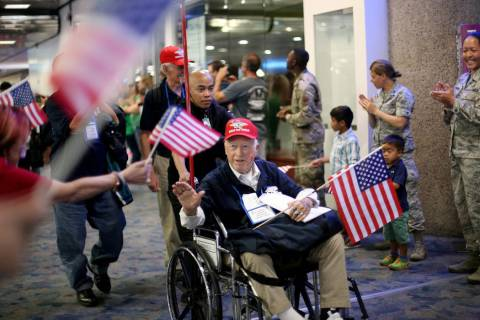 U.S. Air Force veteran Frank Carmean, 94, greets people as they welcome him back from a trip to ...