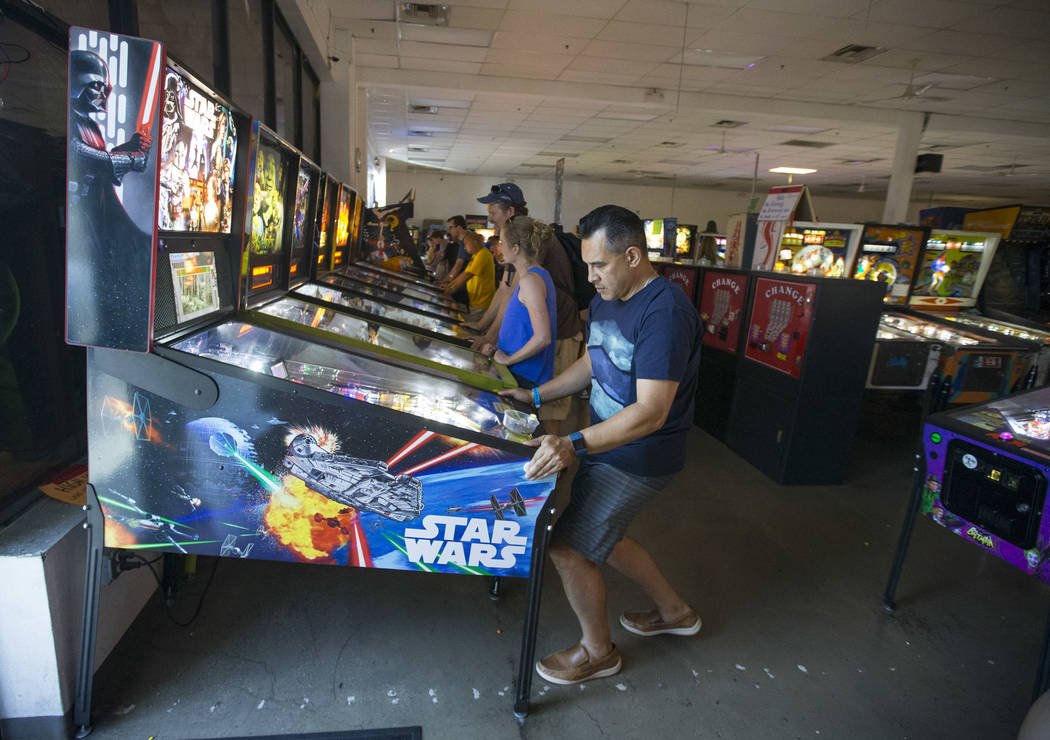 Joel Pastrana of Los Angeles, Calif., plays on a Star Wars pinball machine during a visit to th ...